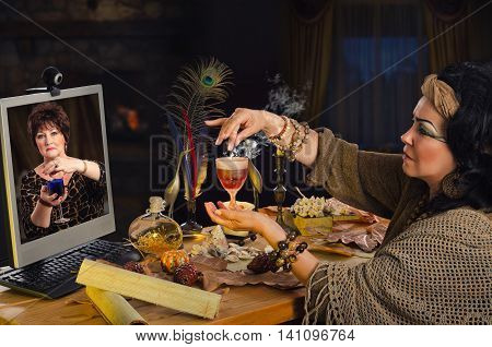 Modern witch teaches how to make love potion for internet client. The psychic holds light brown glass of drink and credits it with magical powder. Mature learner in monitor carefully repeats a recipe