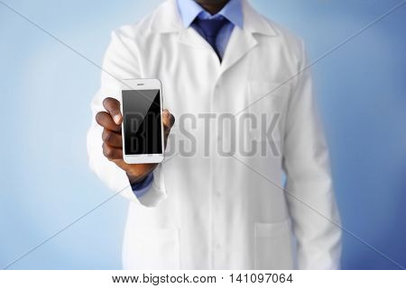 Professional African doctor on light background