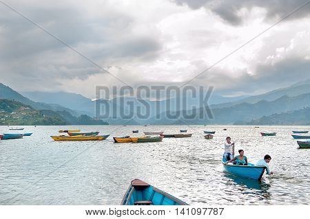 Pokhara Nepal - July 25, 2011: Tourists enjoy boat ride in vast Phewa Lake before a strong thunder-storm, natural colors.