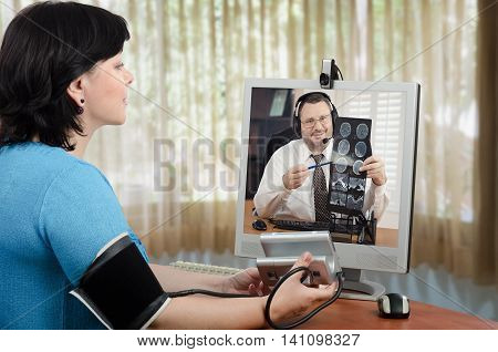 Female virtual patient has just measured her blood pressure and shows results to doctor in her monitor. Male physician in headset is carefully looking at it and explains brain x ray picture