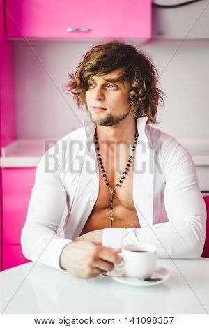 Man in shirt with white cup in the pink kitchen