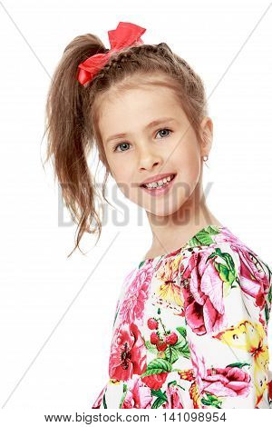 Gentle little girl with a long ponytail down to his shoulders, and a red bow on her head, in a beautiful summer dress. Girl smiling. Close-up - Isolated on white background