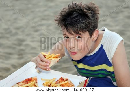 Cute boy eats pizza with potato chips on the beach