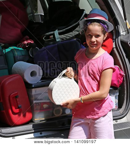 Beautiful Little Girl With Hat Loads The Trunk Of The Car