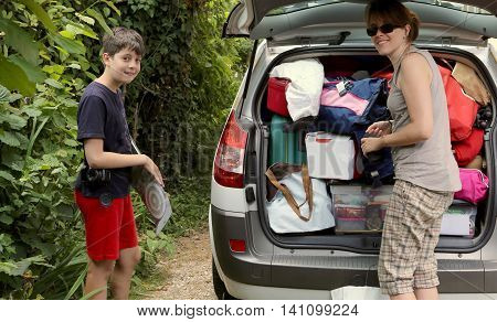 young mother with her son loads the luggage in the car