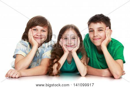 Two teenage boy and girl lie on the floor and looking directly into the camera. 3 people at a children's portrait - Isolated on white background