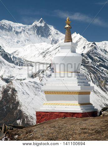 View of white buddhist stupa near ice lake (Kicho Tal) and mount Khangsar Kang Annapurna range Nepal