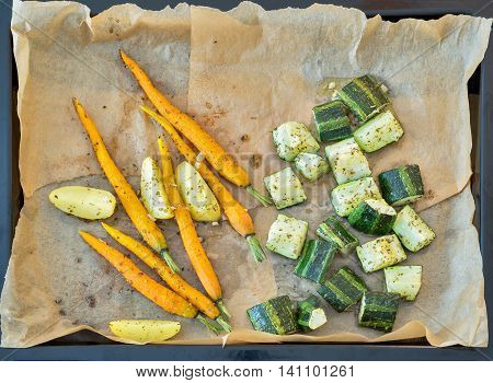 Roasted vegetables in a metallic baking dish. Carrots, potatoes zucchini