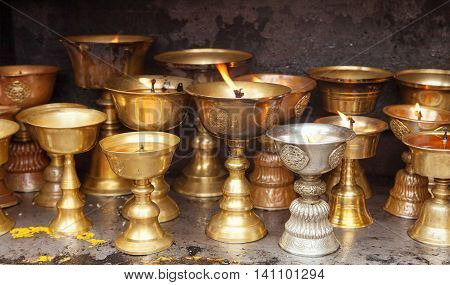 Detail of burning candles in buddhist monastery - Bodhnath stupa in Kathmandu city Nepal