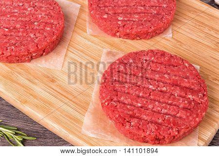 Fresh Burger patties on a wooden cutting board.