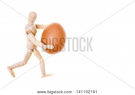 wooden dummy that carries with caution a fragile fresh egg