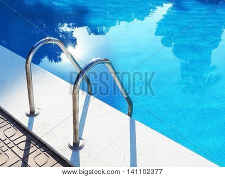 Pool entrance, reflexion of palm trees in the water. Holiday scene