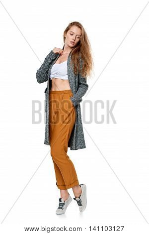 Trendy young woman in pants and long cardigan in full length posing looking down, over white background