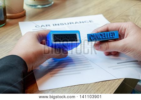 Businesswoman holding approved and cancelled rubber stamp to make a decision on car insurance.