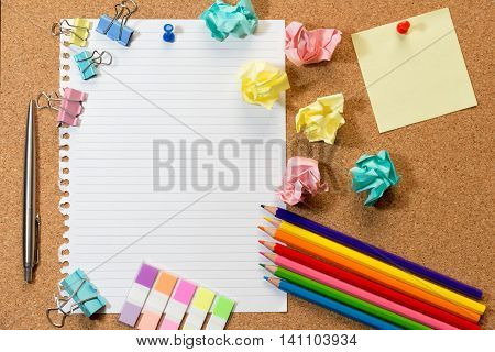 Cork board with blank sheet of paper colorful blank notes color pencil tag trash and push pins.