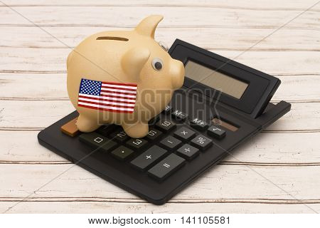 The USD dollar currency A golden piggy bank and calculator on a wood background with US flag