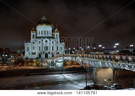 View of the Cathedral of Christ the Saviour in Moscow night winter from the factory Red October. The bridge to the Temple lit lanterns. Moscow River and frozen in the ice.