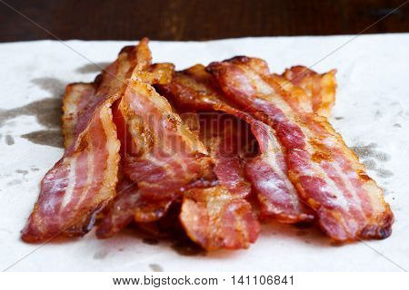 Fried crispy bacon on paper in perspective.