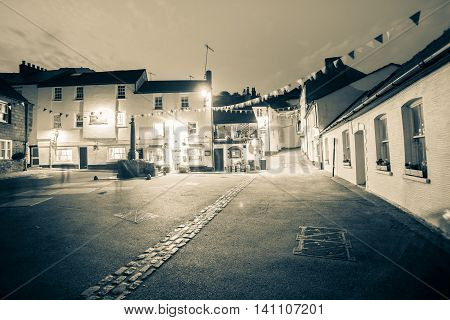 Cawsand England - July 23, 2013: Long exposure split tone image night time in old English coastal village old buildings and shops around town center