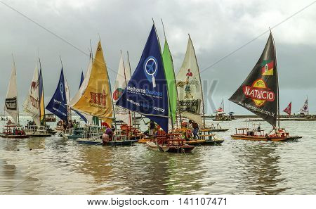 Pernambuco Brazil July 6 2016: An unidentified group of people in Chicken Beach with typical sail boats in Ipojuca City northeast Brazil