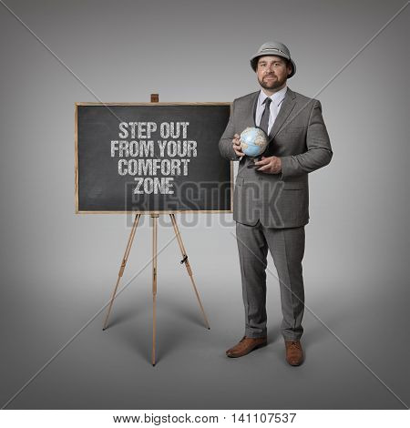 Step out from your comfort zone text on blackboard with businessman holding globe in hands