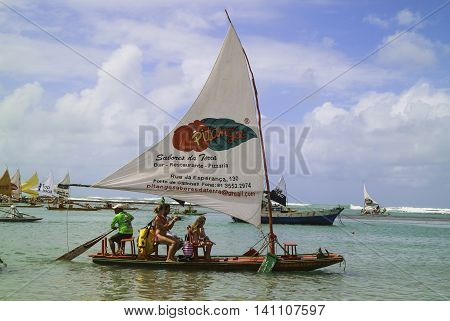 Pernambuco Brazil July 6 2016: An unidentified group of people in Chicken Beach with typical sail boats in Ipojuca City near barrier reef northeast Brazil