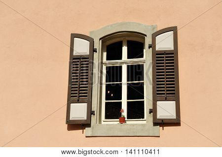 Retro style window on pink smooth facade.