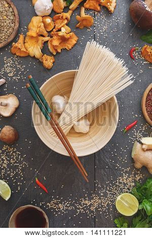 Asian still life with buckwheat soba noodles and chopsticks on  bowl.  Ingredients for vegetarian noodle dish. Top view, vintage toned image