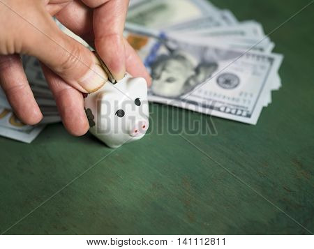 A hand inserting abstract coin in a pig money box US currency in the blurred background. Studio shot with selective focus