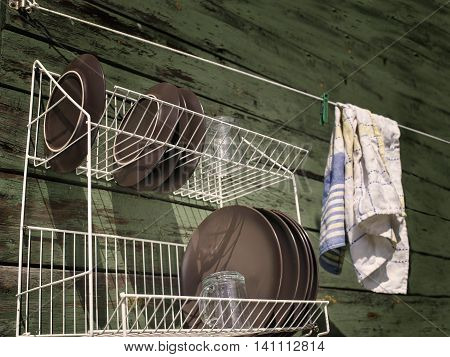 Clean washed dish ware drying on a drainer mounted on the wooden wall angled filtered outdoor shot