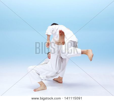 Children are doing Judo throws on the light background