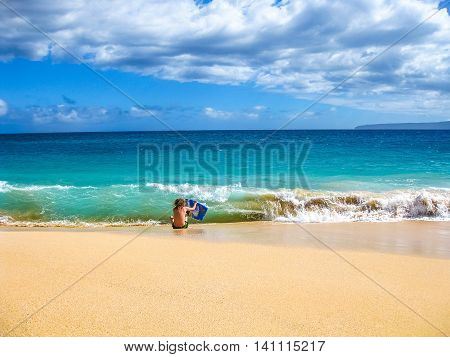 Young boy runs on sand making bodyboarding, Big Beach, Maui in Hawaii, America.