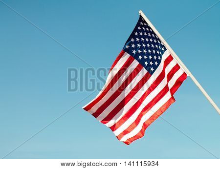 United States flag blows in the wind against a blue sky attached to the wall from the side.