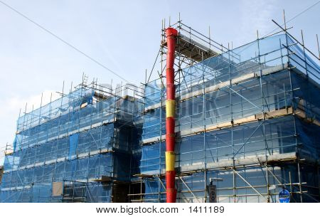 A Building Covered In Scaffolding And Tarpaulin And A Chute.