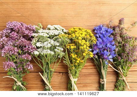 Different types of fresh herbs on a wooden background.
