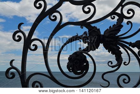 Ocean and sky view through wrought iron gate on the Cliff Walk in Newport, RI.