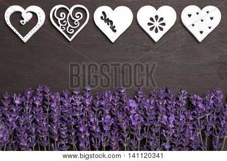 Frame with lavender and wooden heart on a dark background.
