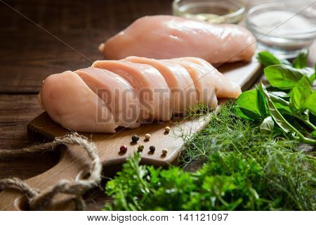 Raw chicken breast fillets and vegetable on wooden cutting board