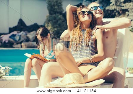 young happy family couple of pretty woman in glasses near muscular man and small girl reading book at swimming pool with blue water sunny summer vacation