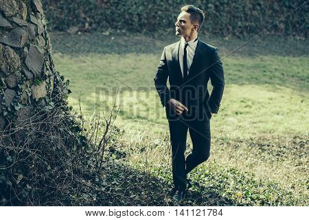 Man half face young handsome elegant model in suit with skinny necktie poses with hand in trouser pocket one leg backward outdoor on natural background