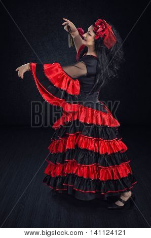 Mature woman dances a waltz with an imaginary partner alone in dark stage. The dancer wears red and black flamenco floor-length gown with frills