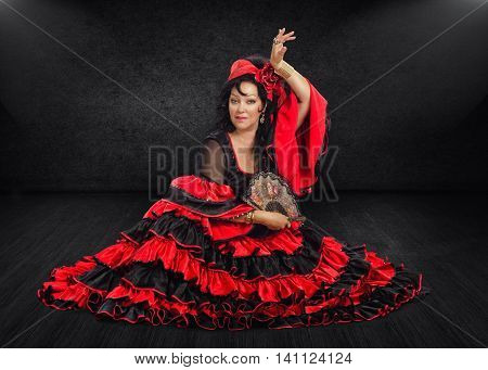Atractive mature female flamenco dancer sits on black stage floor. Black haired woman wears red and black flamenco floor-length gown with frills