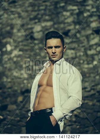 Man bare-chested young handsome sensual model in white shirt gaped open poses with hands in black trouser pockets outside on masonry background