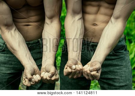 Young men with muscular bodies showing strong hands in fists sunny day outdoor