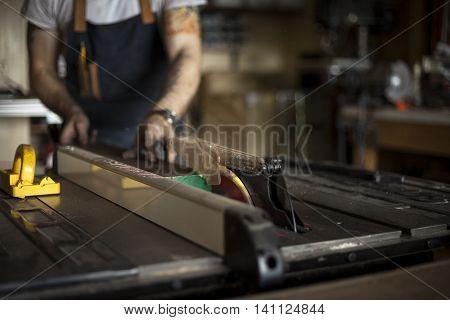 Custom furniture craftsman cuts wood with saw.