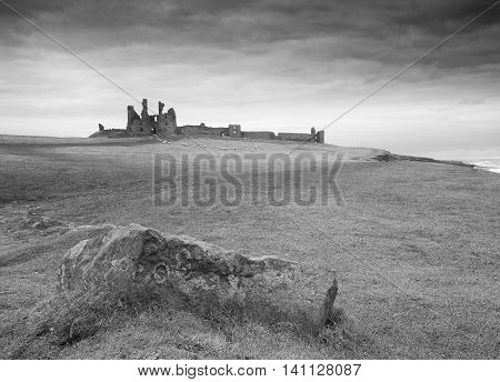A dark view of Dunstanburgh Castle showing a classical elevation view in silhouette beneath a troubled sky