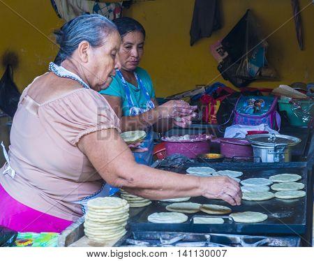 SUCHITOTO EL SALVADOR - MAY 07 : Salvadoran women prepares Popusas in Suchitoto El Salvador on May 07 2016. Popusa is a traditional Salvadoran dish made of corn tortilla