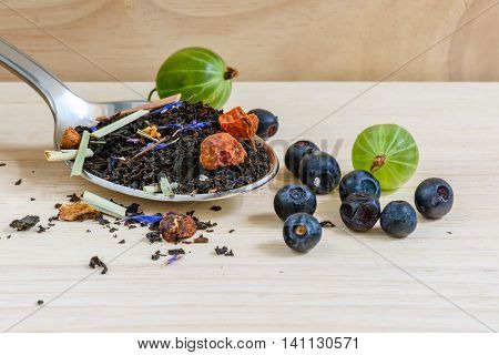 Black tea with different fruits and berries for breakfast. It is tasty healthy and very flavored