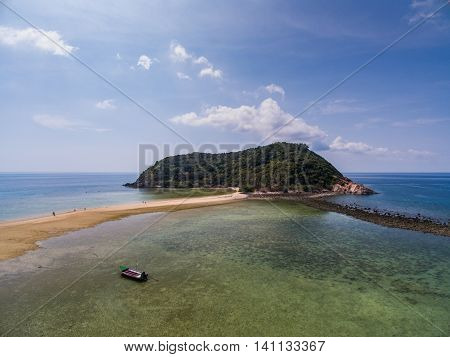 The sandy beach with the island and boat in Thailand