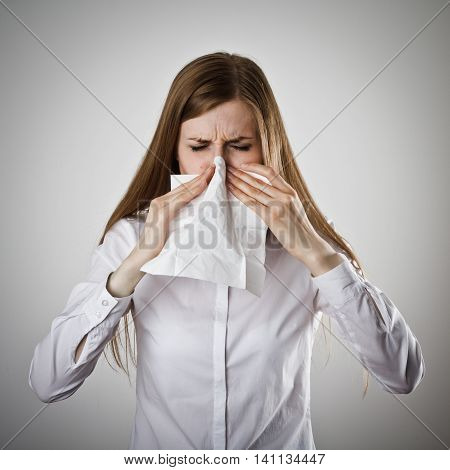 Young woman in white is sneezing. Allergy.